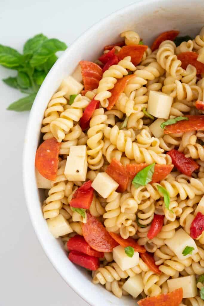 overhead view of italian pasta salad in white bowl with basil sprig nearby