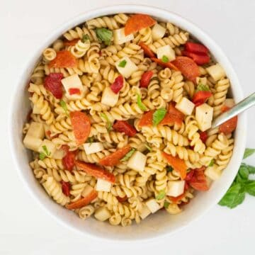 italian pasta salad in white bowl with basil sprig nearby