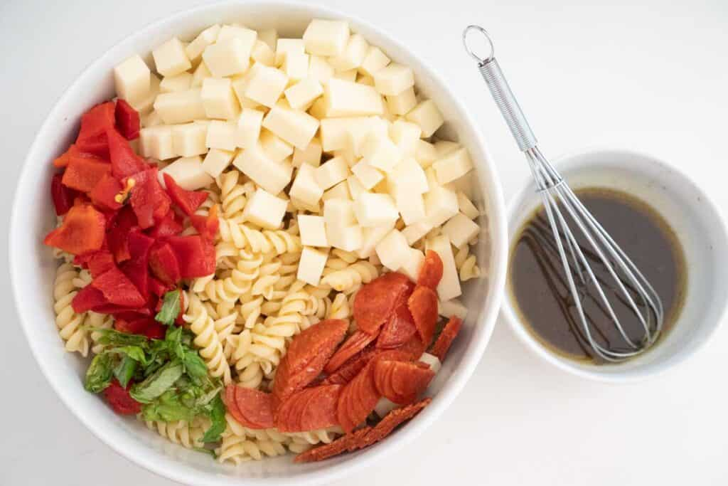 cold italian pasta salad ingredients from overhead in a white bowl with small bowl of dressing with whisk nearby