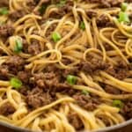 text reading 15 minute mongolian noodles over close up photo of mongolian noodles in skillet with chopped green onion