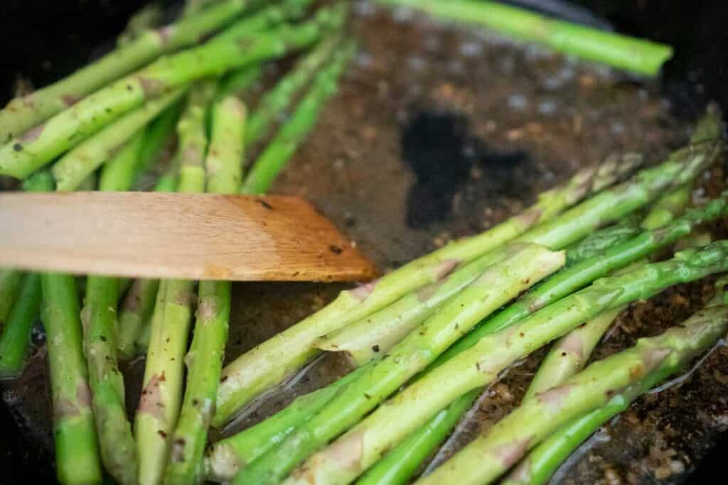 wooden spatula deglazing pan with asparagus and broth