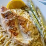 white plate with pasta topped with chicken breast, asparagus and cream sauce and lemon garnish