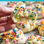 hand holding funfetti cookie with bite taken out with more cookies in background and text reading funfetti cake mix cookies