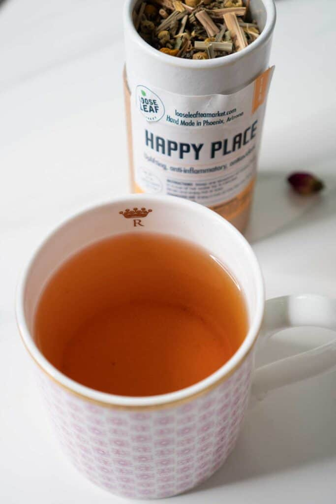 container of happy place tea with mug of tea in front