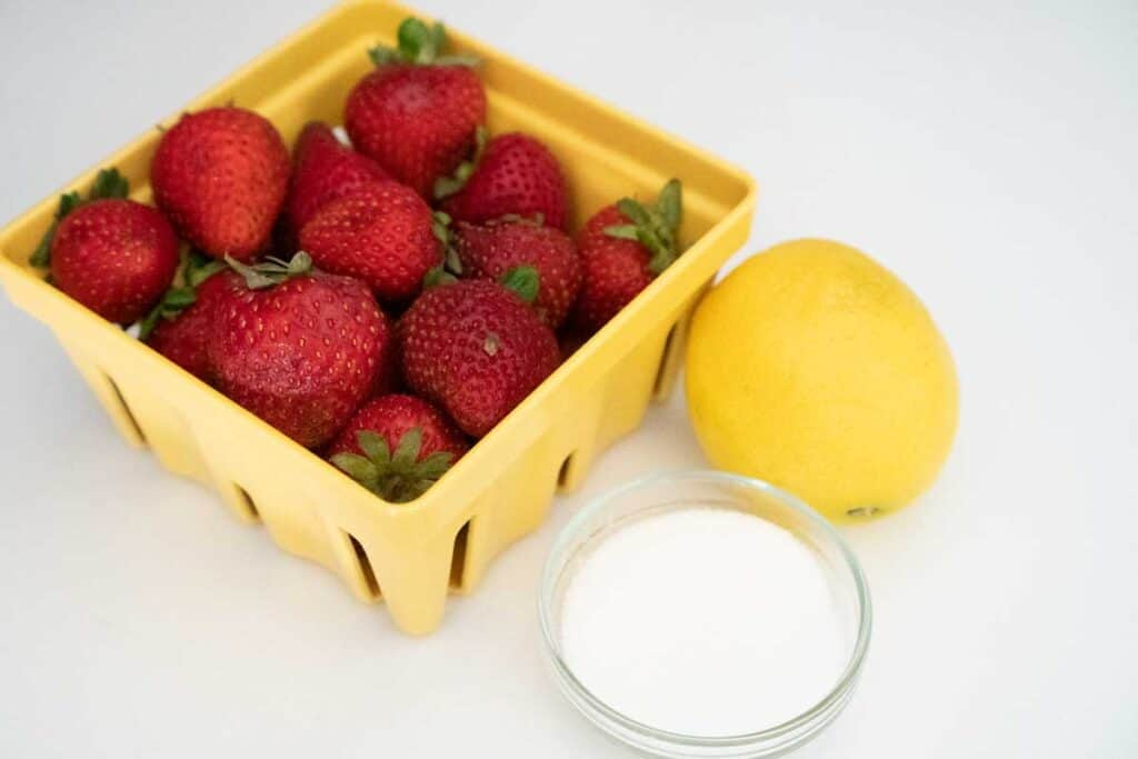 carton of strawberries, lemon, and small glass bowl of sugar
