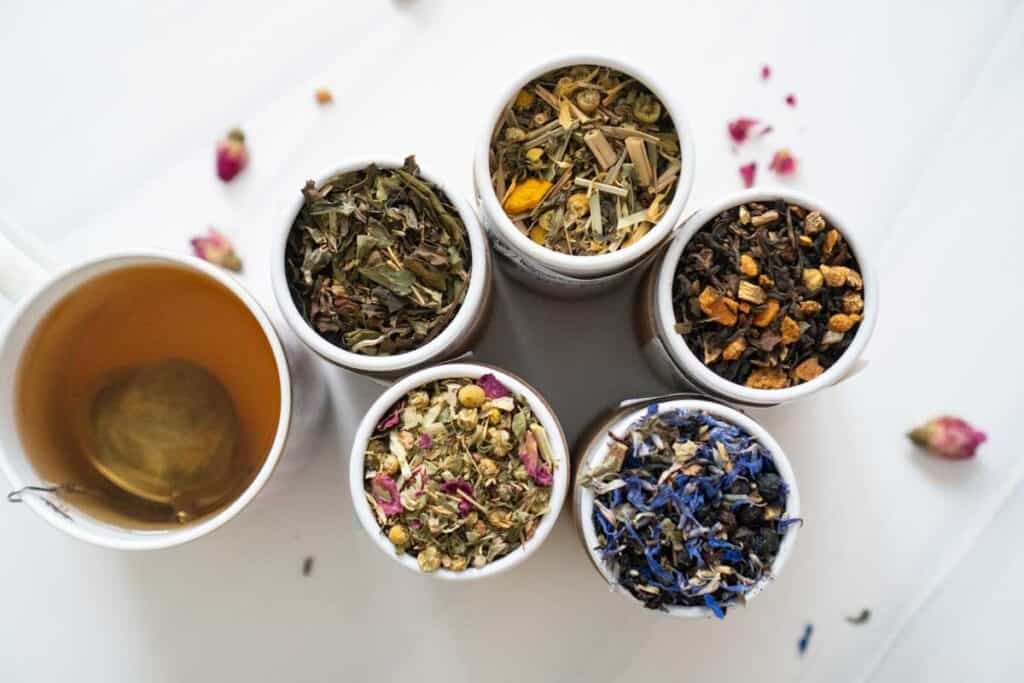 overhead view of five containers of loose leaf tea and china mug with tea steeping in diffuser