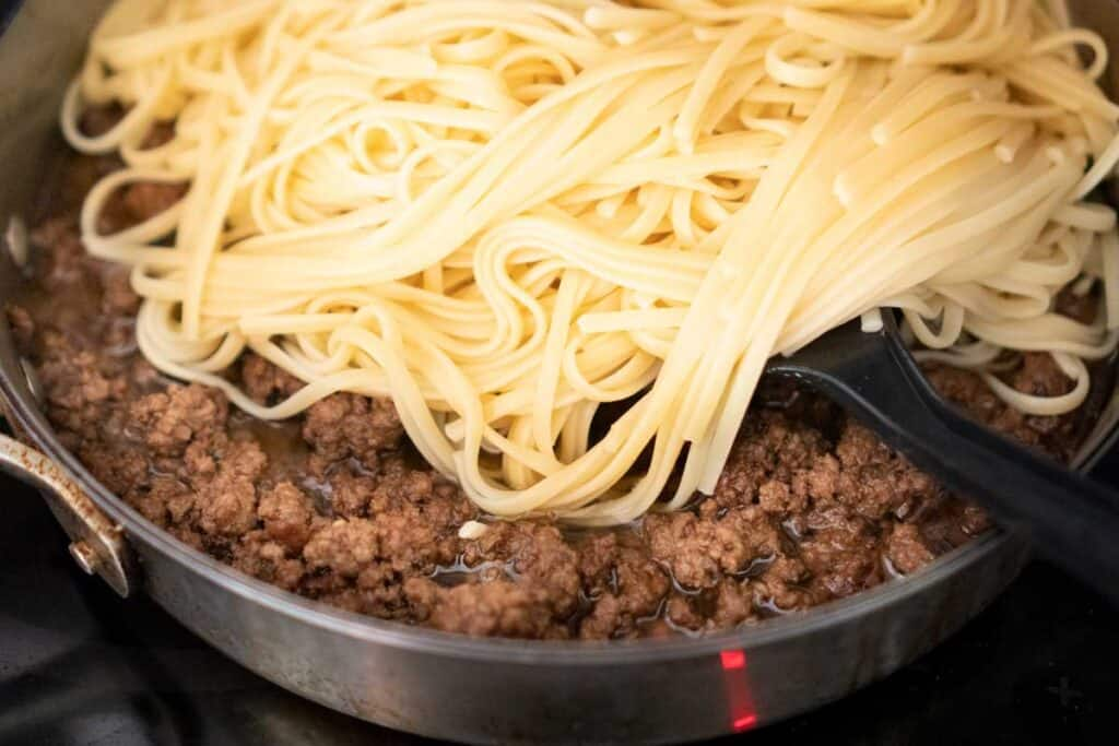 adding noodles to ground beef in pan
