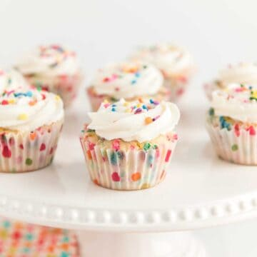 funfetti cupcakes with sprinkles on white cake stand