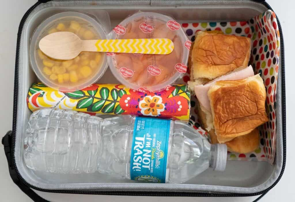 overhead view of lunch box with food and water bottle