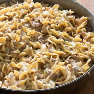 close up of creamy sausage pasta in pan