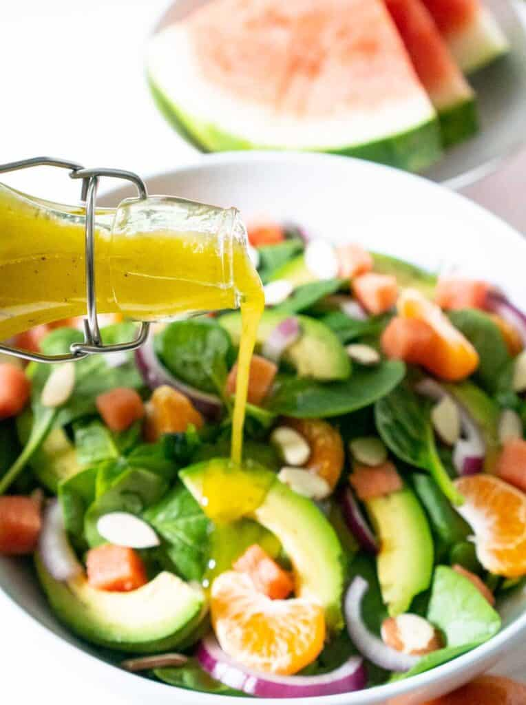 pouring salad dressing from glass bottle onto salad