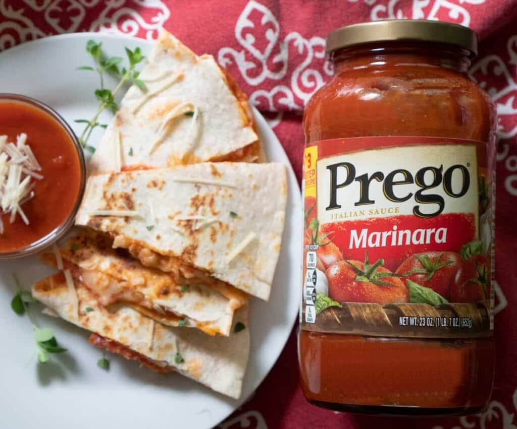 pizza quesadilla on white plate with bottle of prego spaghetti sauce