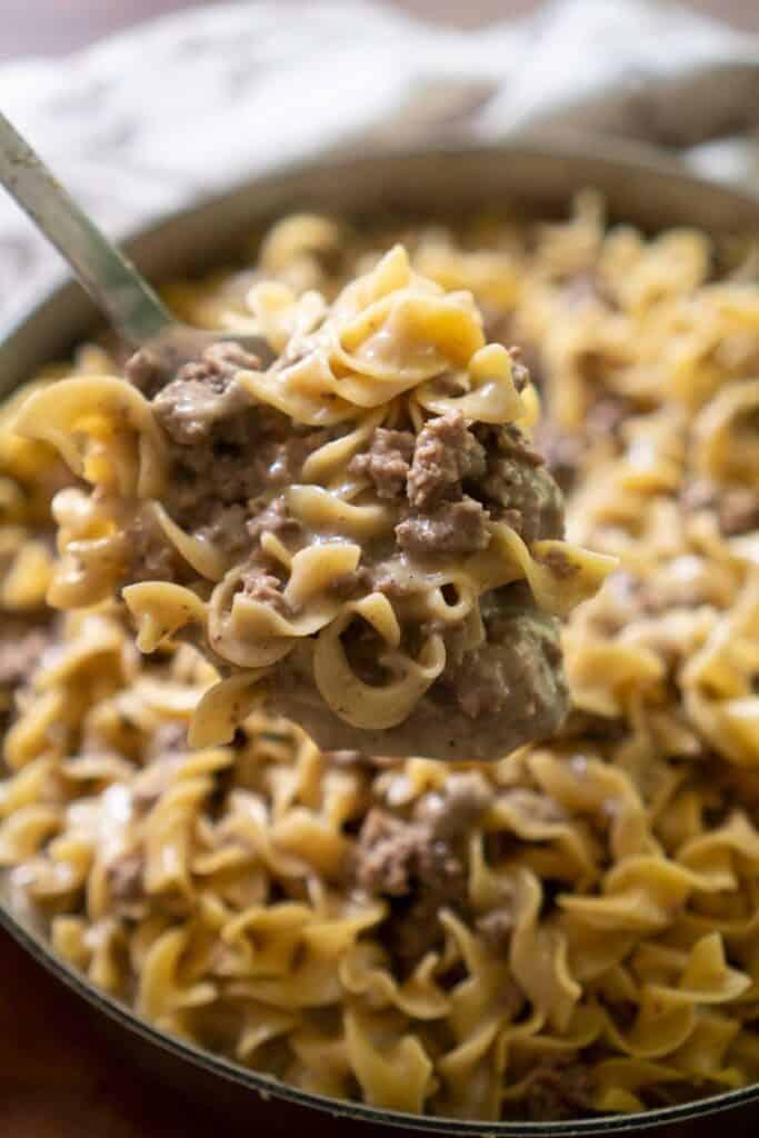 ground beef stroganoff in spoon held over pan