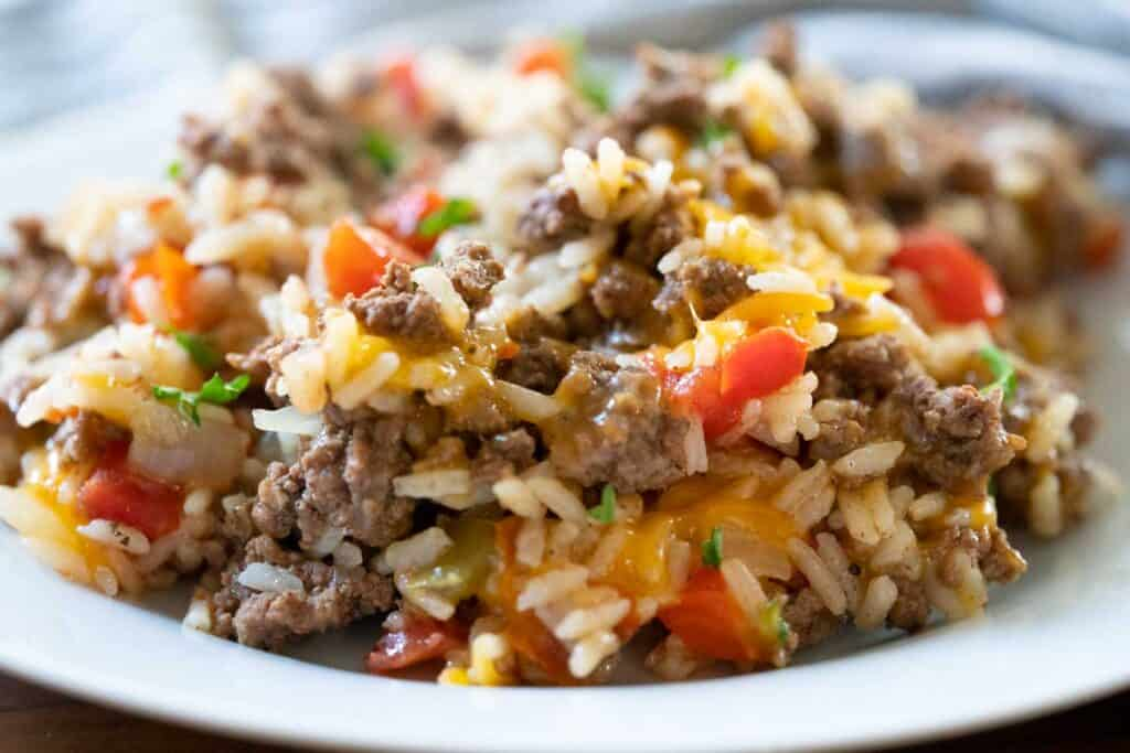 beef and rice with cheese on white plate